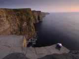 A Couple Lies on Rocks Overlooking the Cliffs of Moher and the Sea Fotografiskt tryck av Jim Richardson