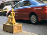 Traffic Whizzes by a Buddha Statue on a Sidewalk Photographic Print by Alison Wright