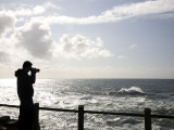 A Silhouetted Photographer Takes a Pictures of the Rugged Coastline at Sunet Photographic Print by Michael Hanson