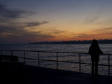 A Silhouetted Woman on a Pier Looks across to a Lighthouse at Sunset Photographic Print by Todd Gipstein