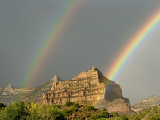 A Pair of Rainbows after a Storm over a Rocky Outcrop Photographic Print by Ira Block