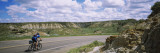 Man Cycling on a Road, Badlands, Theodore Roosevelt National Park, North Dakota, USA Wall Decal by  Panoramic Images