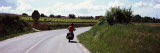 Man Riding a Motorcycle on a Road with Vineyards in the Background, Penedes, Catalonia, Spain Wall Decal by  Panoramic Images
