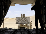 A Forklift Loads Cargo onto a C-130 Hercules on a Dirt Runway in Tarin Kowt, Afghanistan Photographic Print by  Stocktrek Images