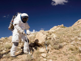 Astronaut Stands Beside a Core Sampling Tool on the Edge of Meteor Crater During Desert Rats Photographic Print by  Stocktrek Images