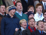 Prince William sings the National Anthem still wearing his wooly hat while his brother Harry does t Fotografisk tryk