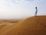 Man Standing on Sand Dune Looking Out on Arabian Desert Photographie par Christian Aslund