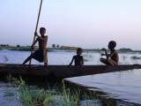 Three Boys Play on a Canoe (Pirogue) on the River in Mopti Photographic Print by Dan Herrick
