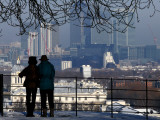 Mature Couple Enjoying Winter View of the Maritime Museum and Canary Wharf from Greenwich Park Photographic Print by Doug McKinlay