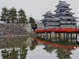 Matsumoto Castle with Moat, Stone Work and Red Wooden Bridge Photographic Print by Frank Carter