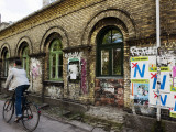 Cyclist in Freetown Christiania, with Anti European Union Posters on Wall Photographic Print by Christian Aslund