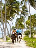 Tourists Horseback Riding Along Beach Trails Photographic Print by Greg Johnston