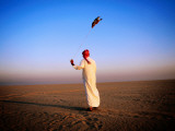 Arab Handler Swinging Lure During Hunting Falcon Training Exercise in Desert Photographie par Mark Daffey