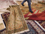 Salesman Walks on Carpets for Sale at Carpet Factory Photographic Print by Holger Leue