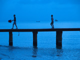 Two Boys Walking on Occidental Grand Cozumel Resort Pier at Sunset Photographic Print by Dennis Johnson