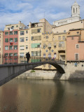 Woman Crossing Pont D'En Gomez Above Onyar River before Colourful Old Buildings Photographic Print by Craig Pershouse