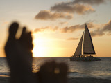 Relaxing Feet and Catamaran at Sunset Seen from Bucuti Beach Resort on Eagle Beach Photographic Print by Holger Leue