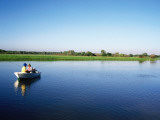 Anglers in Boat Fishing for Barramundi in Yellow Water Wetlands Photographic Print by Holger Leue