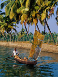 Man Paddling Small Canoe with Sail Near Ayiramthengu Photographic Print by Craig Pershouse