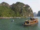 Tourist Cruise Boat Passing Typical Floating Village Among Limestone Islands of Halong Bay Photographic Print by Anders Blomqvist