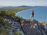 Woman Looking Down over Island from Rock Ridge Photographic Print by Andrew Peacock