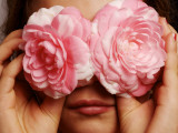 Young Girl Holding Camellia Flowers over Her Eyes Photographie par Oliver Strewe