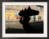 A Boy Carrying Bottles on His Head Passes by a Wall with Pictures of Haitian President Renel Preval Framed Photographic Print by Ariana Cubillos