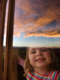 Portrait of Young Girl at Window with Reflection of Clouds at Sunset Photographic Print by Will Salter
