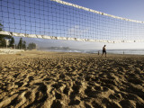 Person Jogging Near Volleyball Net on Manly Beach, Early Morning Photographic Print by Oliver Strewe