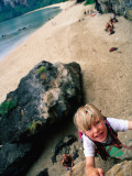 Young Boy Climbing Rocks Above Beach Photographic Print by Philip & Karen Smith