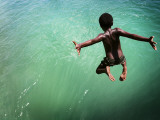 Torres Strait Islander Boy Leaping into the Sea, Seisia, Cape York Fotografie-Druck von Tim Barker