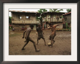 A Group of Panamanian Youths Slide Through the Mud During a Pick-Up Game of Soccer Framed Photographic Print