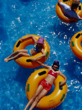 Young Girls Floating in Rubber Rings in Swimming Pool Photographic Print by Richard l'Anson