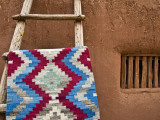 Woven Mat with Native American Indian Motif Against Mud-Brick Wall Photographic Print by Ray Laskowitz