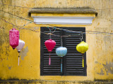 Lanterns Hanging Besides Bright Yellow Wall Photographic Print by Tony Burns
