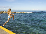 Girl Jumping into Sea at Clovelly Bay Photographic Print by Oliver Strewe