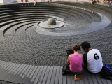 Couple Looking at the Spiral Fountain at the Sydney Convention Centre, Darling Harbour Photographic Print by Manfred Gottschalk