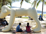 People Sitting under Dog Statue on Patong Beach Photographic Print by Austin Bush