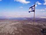 The Blue and White Flag of Israel, the Star of David Flies over the Deserts of Masad Photographic Print by Russell Mountford