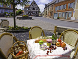 Cheese, Cherries, Apples and Champagne on Cafe Table with Half-Timbered House in Background Fotografie-Druck von Barbara Van Zanten