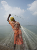 Man Tossing Weighted Net into Shallow Water to Catch Shrimp Photographic Print by April Maciborka