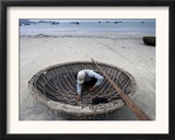 A Vietnamese Fisherman Does Repairs on His Basket Boat on a Beach Framed Photographic Print