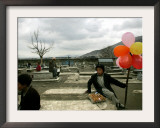 An Afghan Boy Sits on a Grave Plot and Sells Balloons and Eggs as Others Relax Framed Photographic Print
