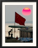 A Girl Rests on a Boat Below the Chinese National Flag Framed Photographic Print