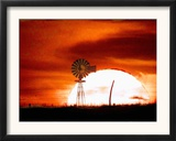A Blazing Sun Drops Behind a Windmill Framed Photographic Print