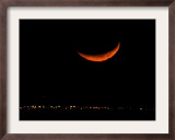 A Crescent Moon Dwarfs the Lights of Fort Riley Army Base in Central Kansas, January 22, 2007 Framed Photographic Print by Charlie Riedel