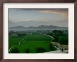 An Afghan Man Rides His Bicycle on a Dirt Road on the Northern Edge of Kabul, Afghanistan Framed Photographic Print by David Guttenfelder