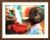 An Unidentified Baby is Fed at a Home for Hiv/Aids and Abandoned Children Framed Photographic Print