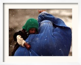 An Afghan Woman Holding Her Child Throws Back Her Burqa to See Her Way Along a Muddy Alley Framed Photographic Print