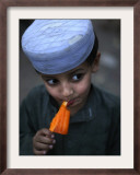 Boy Eats an Ice Lolly in a Neighborhood on the Outskirts of Islamabad, Pakistan Framed Photographic Print
